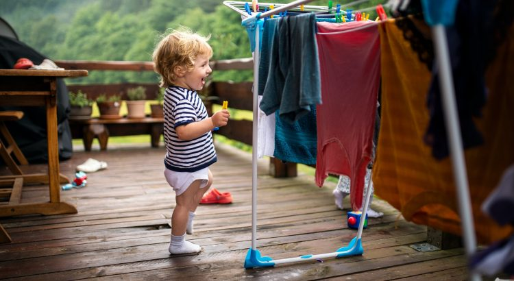 Toddler children outdoors in summer, playing with clothes drying hanger.